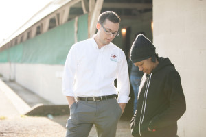 Chris Wong prays with an employee on the Backside of Churchill Downs.