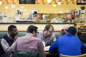 Josh Hildebrand, center, reads from the Gospel of John with two Arab-American men, right, at a local bakery in Dearborn, Michigan.
