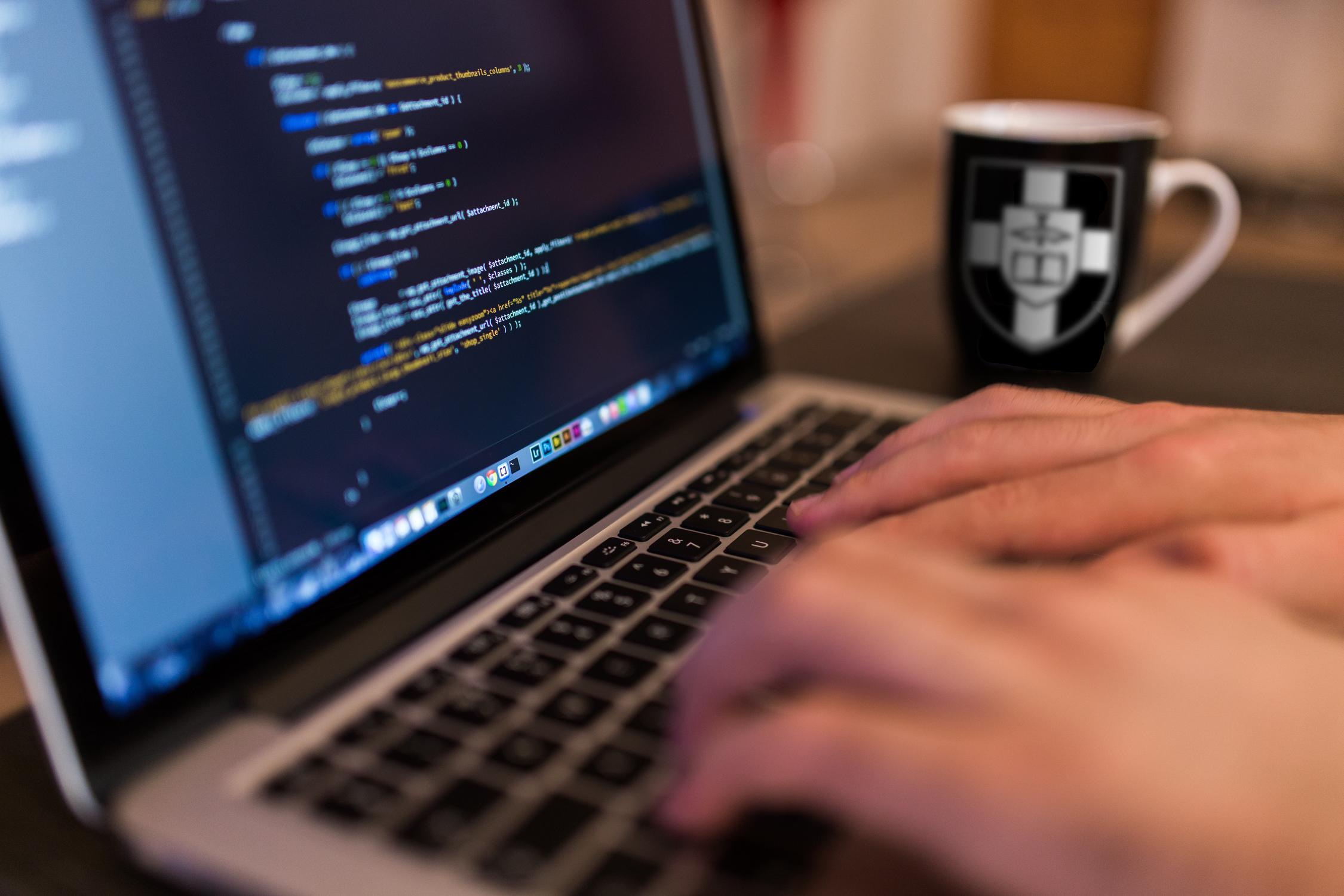 Hands at laptop keyboard writing code